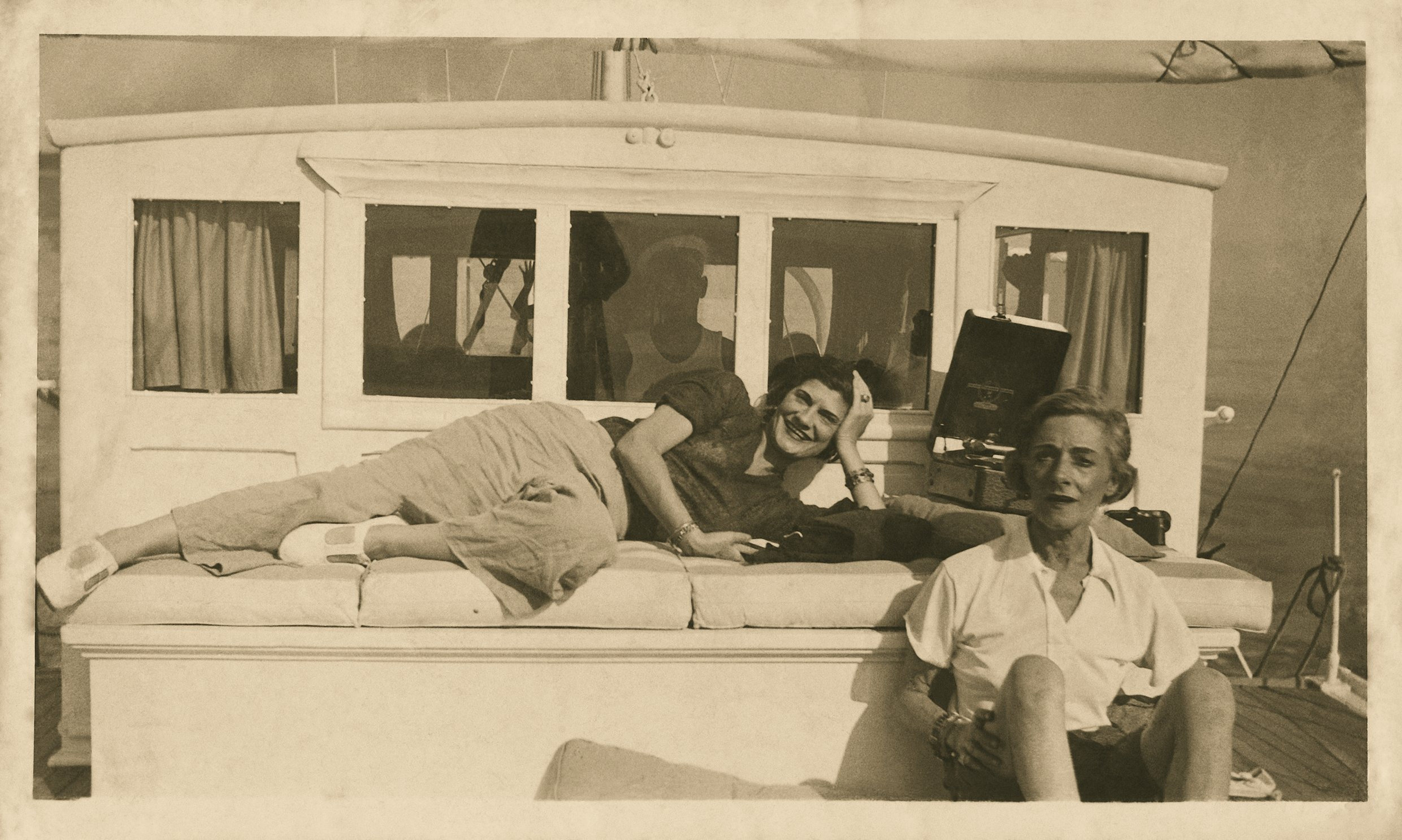 Black and White photograph of Gabrielle Chanel and Roussey Sert enjoying themselves on a boat circa 1935