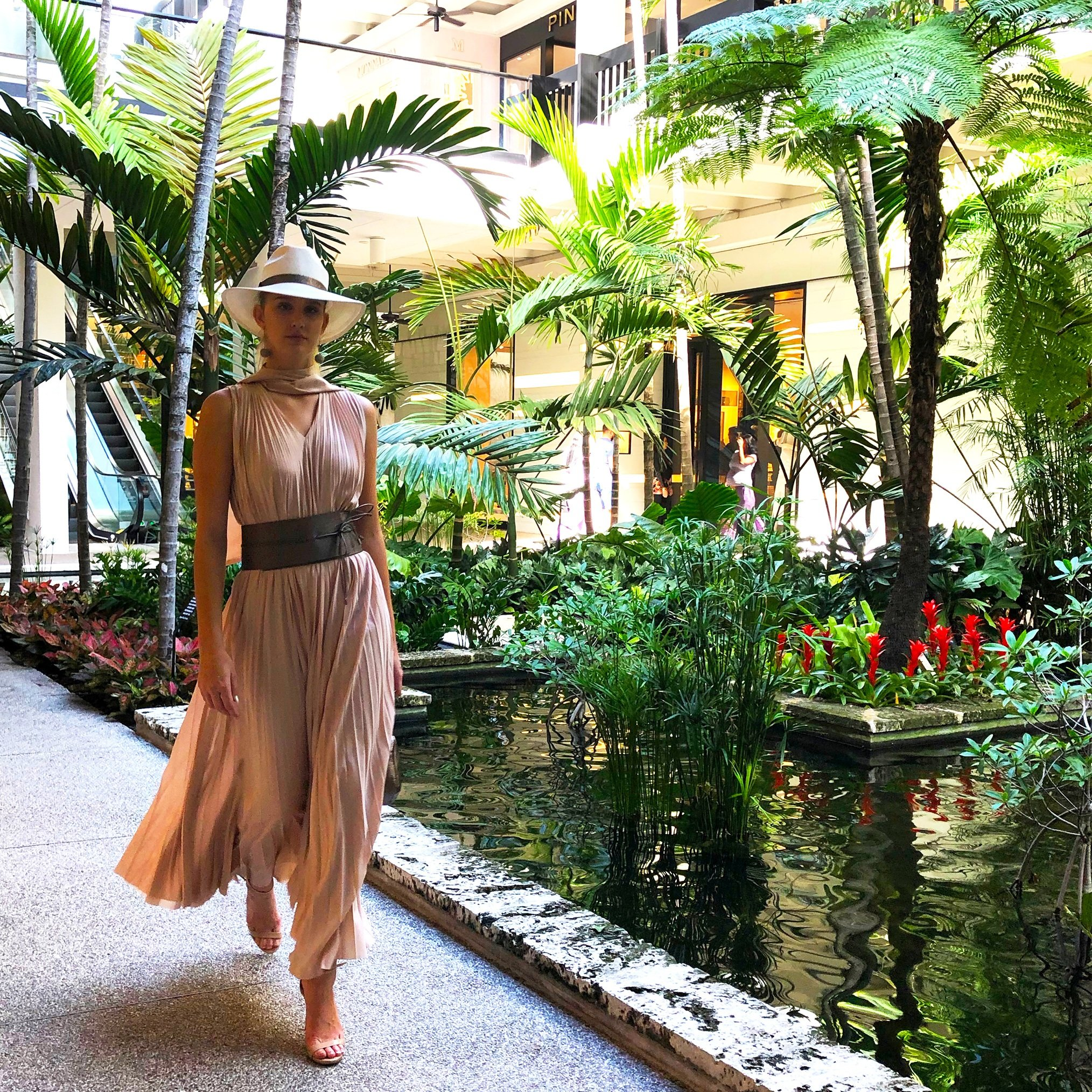 Model strolling by the signature Bal Harbour koi ponds wearing a Fabiana Filippi pleated nude chiffon dress