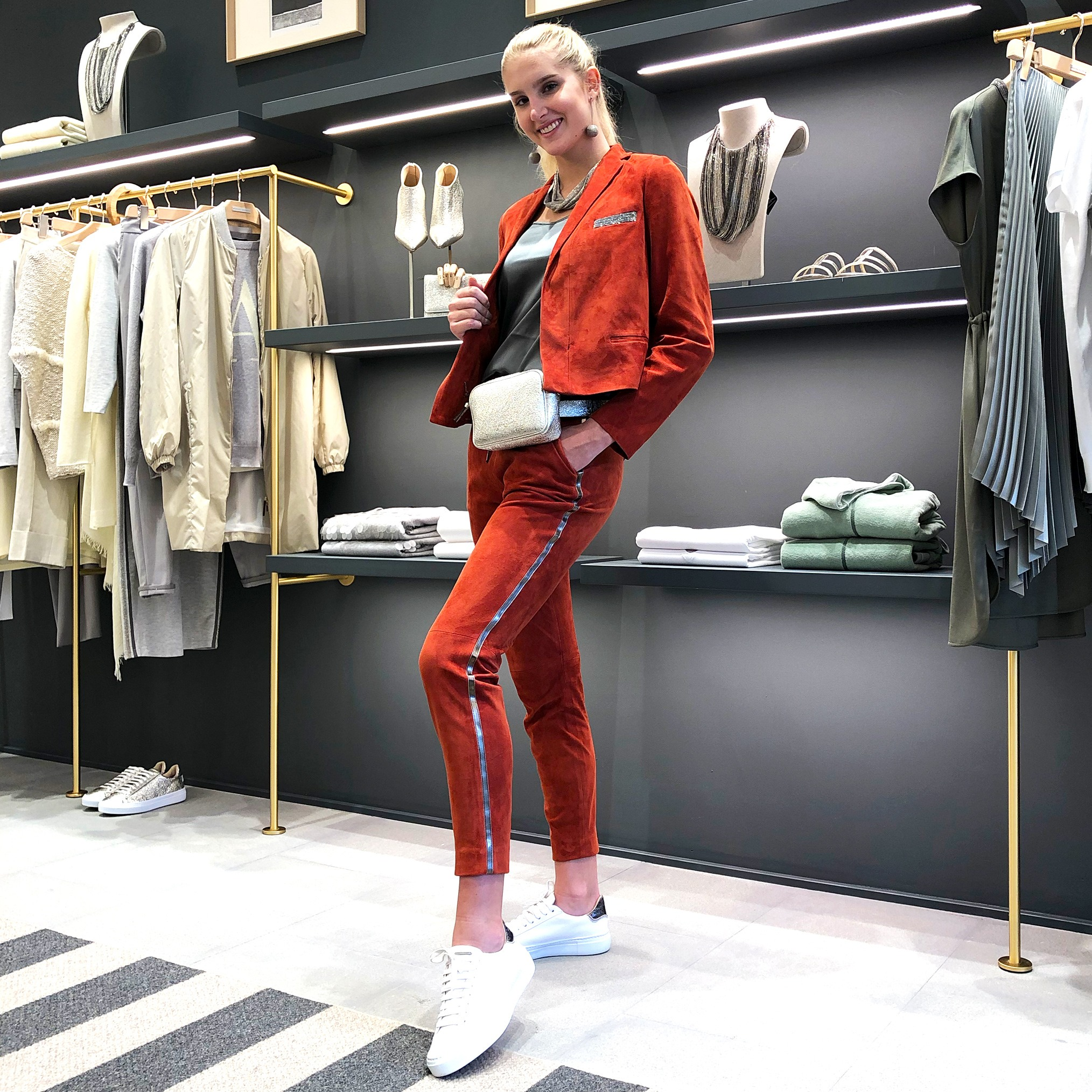 Model inside Fabiana Filippi Bal Harbour wearing a matching suede jacket and cropped trousers in clay orange