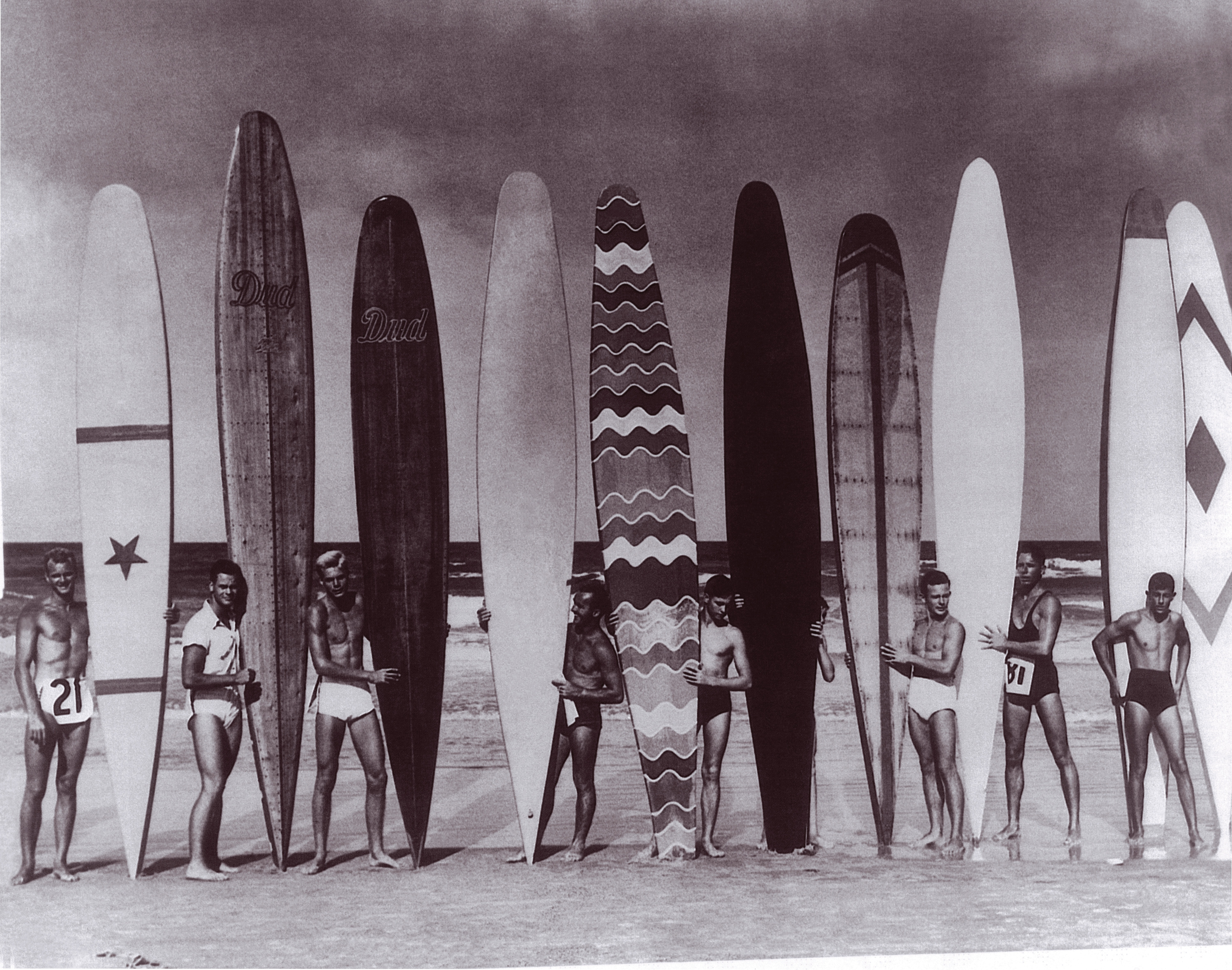Black and white image of Stanley Whitman and his brothers Bill and Dudley with other surfers at Daytona Beach circa 1934