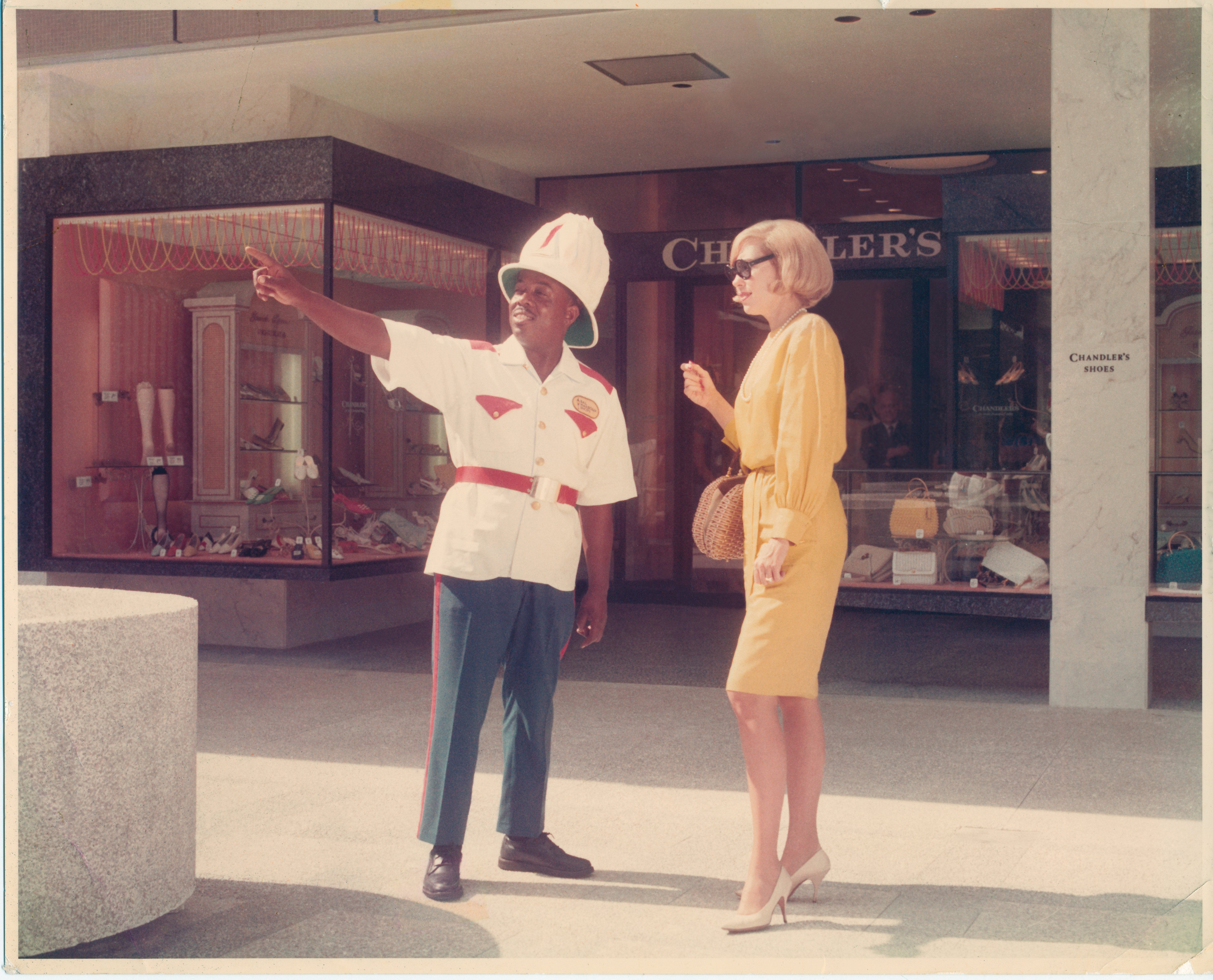 "Employee working as ""Frazier"" the iconic Bal Harbour Shops attendant dressed in a white and red Bahamian police uniform providing guidance to a shopper."
