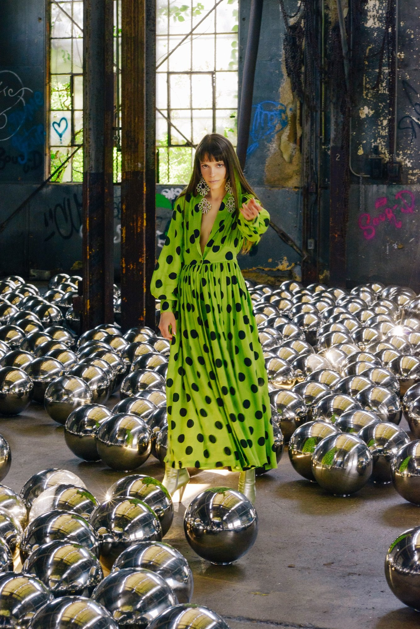 Pari Ehsan wearing a Todd Oldham dress with black polka dots and green satin amongst Yayoi Kusama's Narcissus Garden installation in New York last summer.