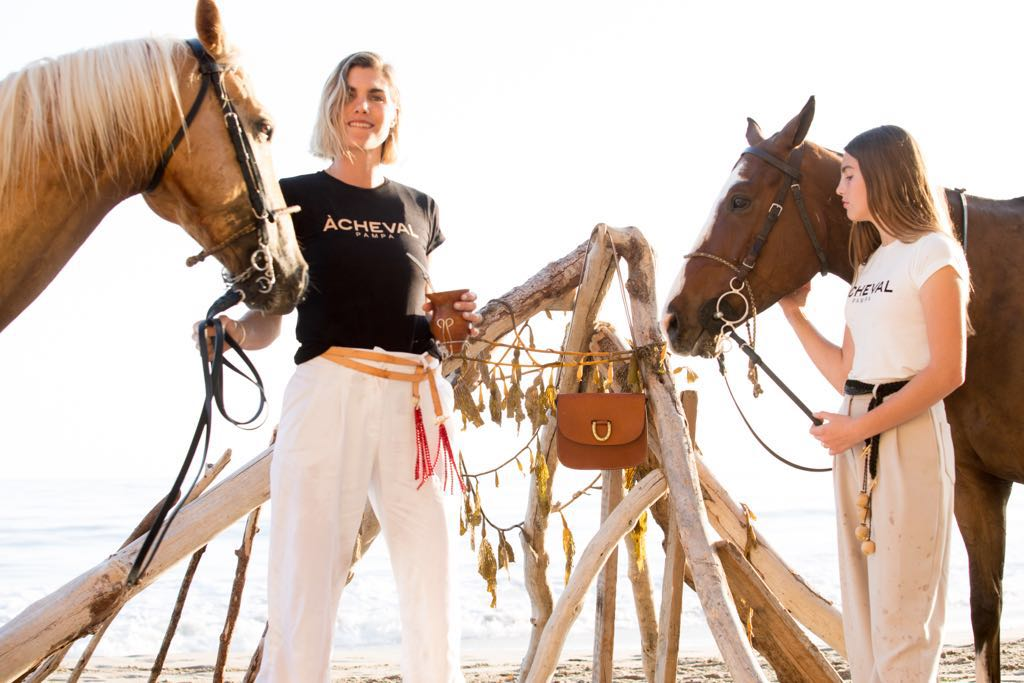 Delfina Blaquier wearing the ÀCHEVAL pampa tee in Black paired with the Al Boleo pants in White and styled with the Tientos belt. Delfina Blaquier's daughter, wearing the ÀCHEVAL pampa tee in White paired with the Al Boleo pants in Beige and styled with the Boleadoras belt.