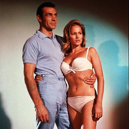 Actor Sean Connery as James Bond posing with actress Ursula Andress as Honey Ryder in the first James Bond film, Dr. No.
