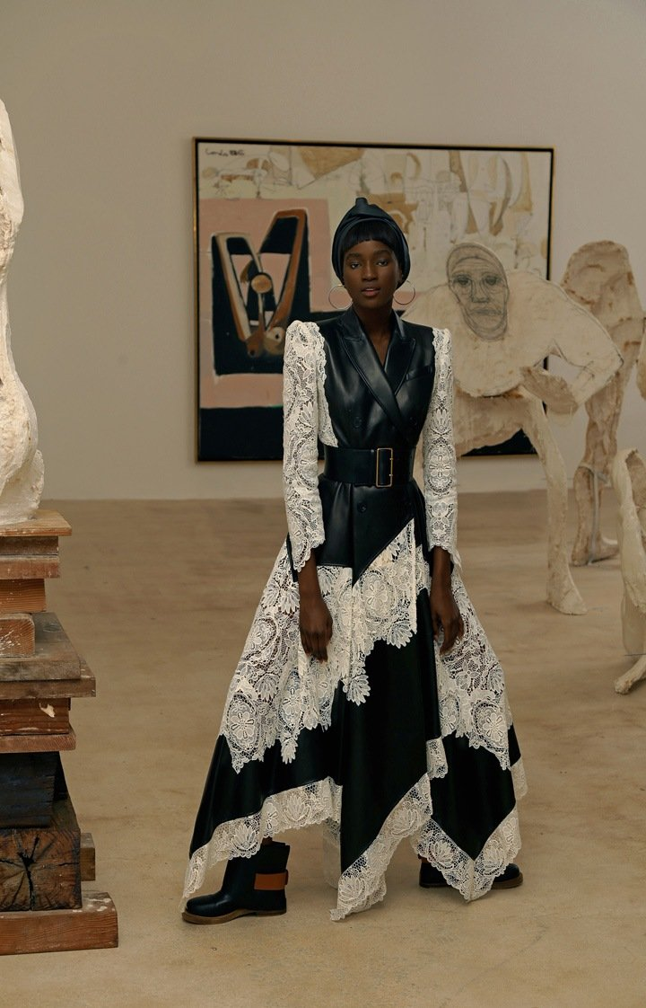 Alexander McQueen dress, boots with buckles and oversized waist belt. Lana silver hoops, available at Saks Fifth Avenue. Artwork by Thomas Houseago (foreground) and George Condo.