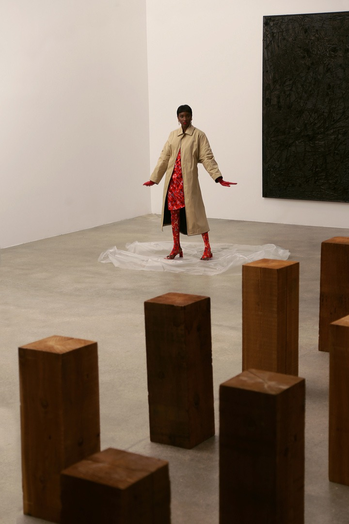 Balenciaga khaki oversized coat, red Eiffel Tower-print dress and leggings, open toed mules and monogrammed jewelry. Artwork by Carl Andre (foreground) and Rashid Johnson.