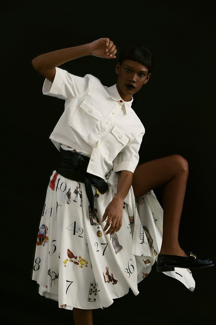 Heron Preston white short-sleeve button-up, available at The Webster. Monse silk pleated platform skirt, available at Saks Fifth Avenue. Prada black leather loafers with gold detail.
