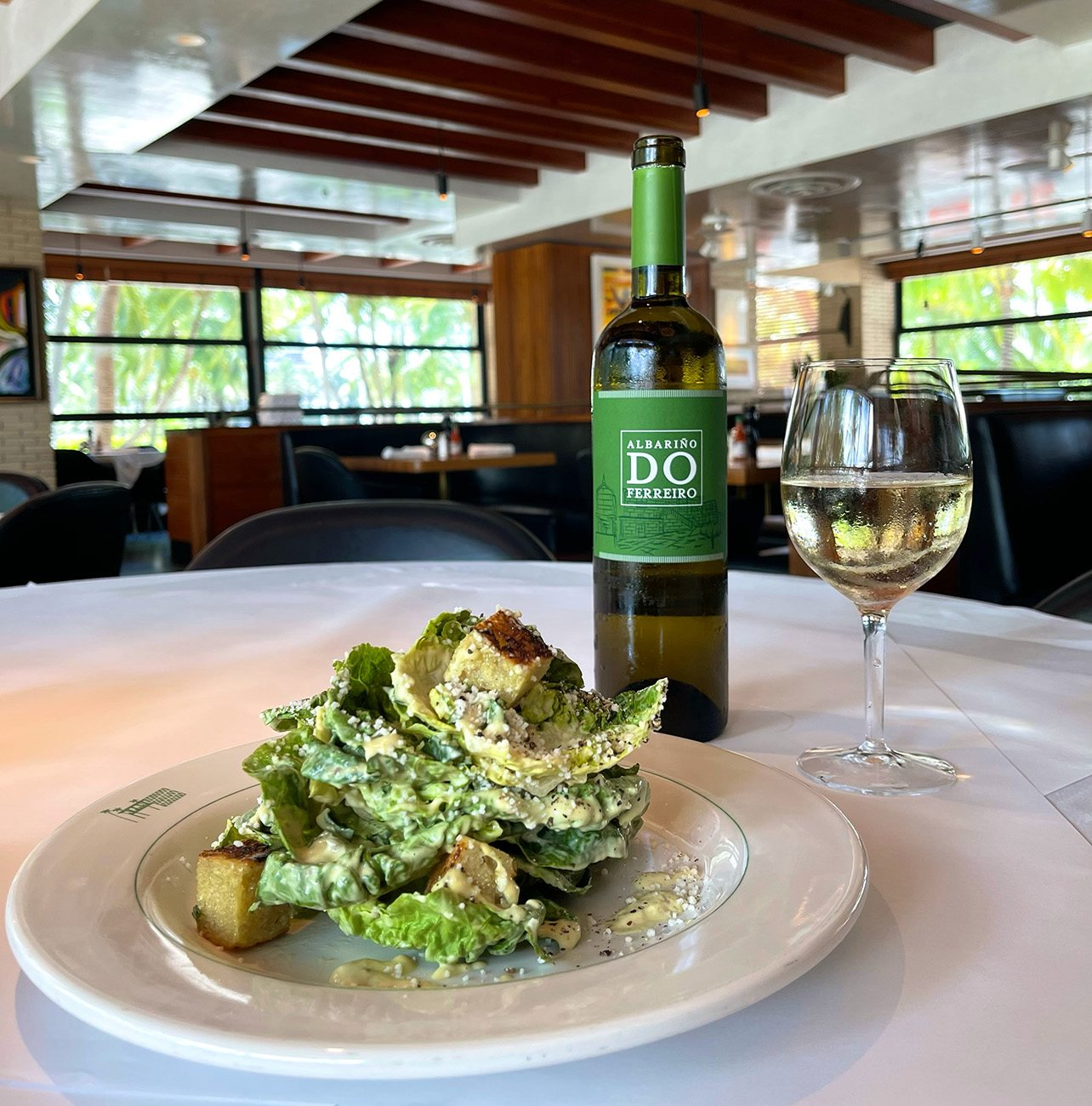 Hillstone Caesar salad paired with a glass of natural white wine
