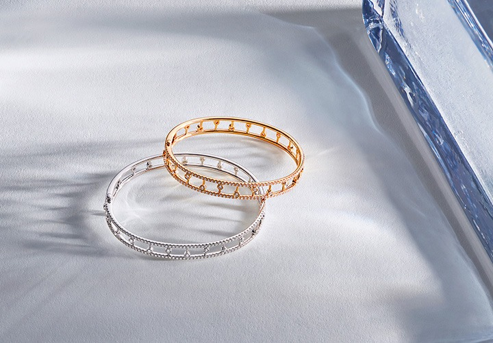 Dewdrop Bangle featured in White Gold and Rose Gold from the De Beers Dewdrop Collection