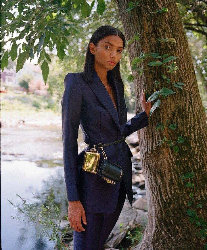 Alexander McQueen blazer, pants, Myth Cylinder clutch with attached harness and gold mini clutch.