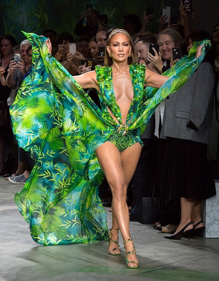 A 50-year-old Jennifer Lopez stole the spotlight at the Versace Spring 2020 show wearing a reprisal of the plunging palm frond frock she wore in 2000.