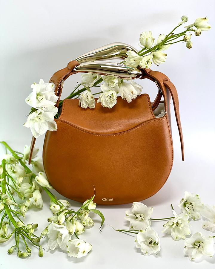 Chloé's Kiss Leather Hobo Bag in Arizona brown with a semicircular silhouette, abstract bar handle, and top magnetic flap closure.