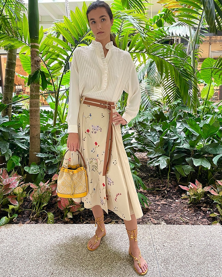 Tory Burch T monogram jacquard bucket bag, ruffle-front blouse, embroidered pleated skirt and capri flat lace-up sandal from the SS21 collection.