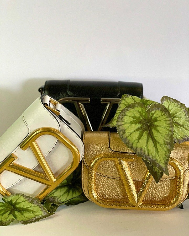 Small Valentino Garavani Supervee crossbody bags in calfskin leather with maxi VLogo Signature. Pictured in three colorways : Optic White, Black, and Gold.