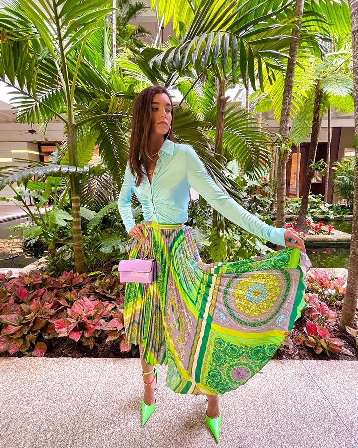 Versace blouse, Barocco mosaic-print pleated skirt, Purple Medusa bag, Palazzo dia crystal ring and pendant necklace and green heels from the SS21 collection.