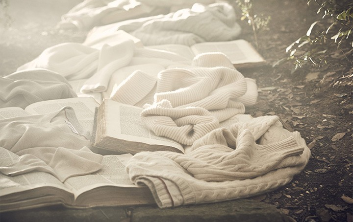 Brunello Cucinelli campaign image for Never Ending Stories with books and sweaters lining the ground of a forest.