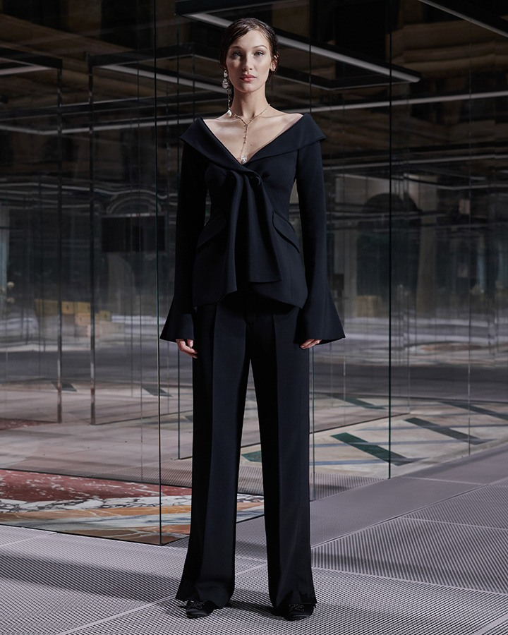 Bella Hadid wears an off-the shoulder flare-sleeved wool top and black trousers.