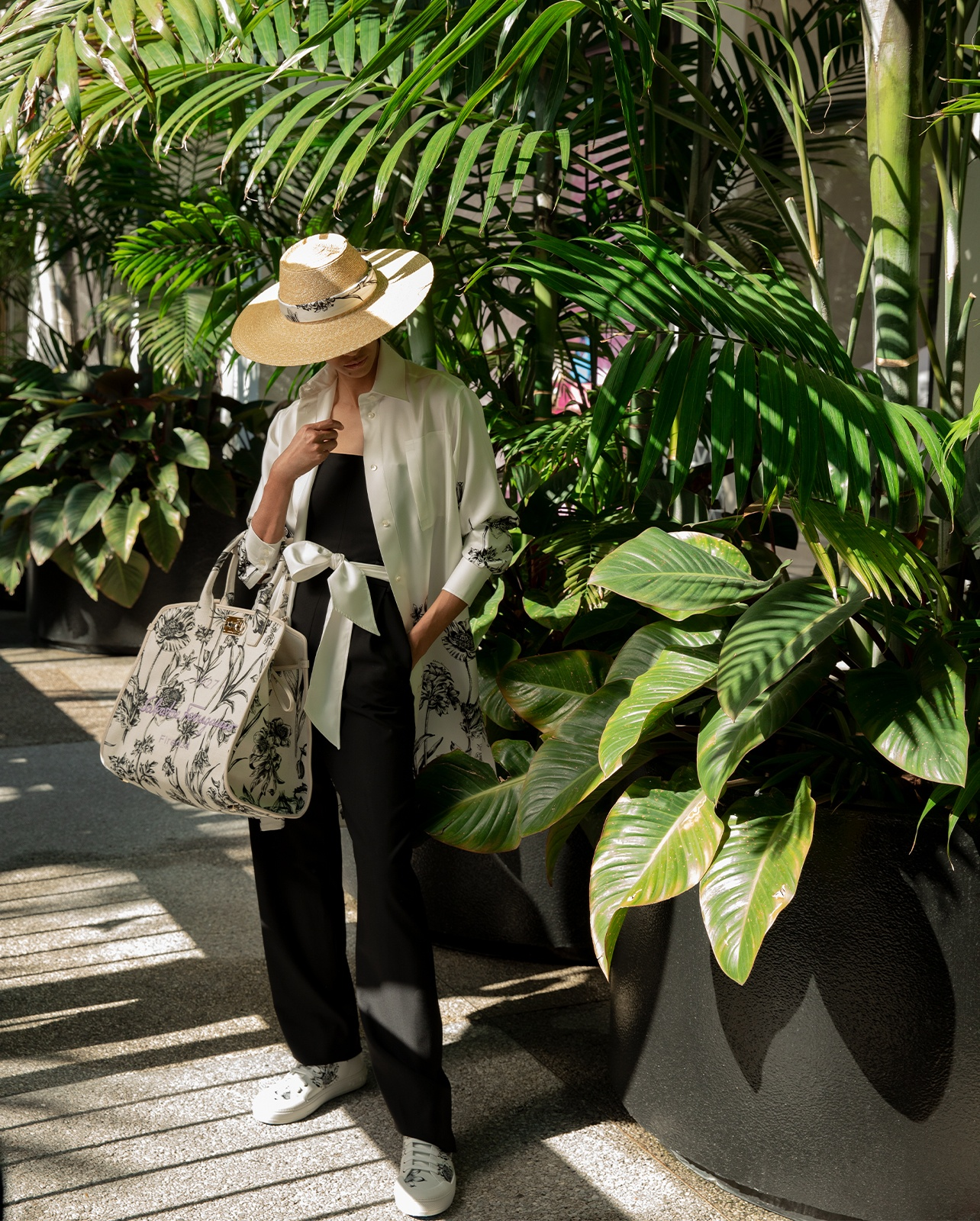 Salvatore Ferragamo black strapless jumpsuit, styled with silk kimono, hat, sneakers from the Tuscan Wildflower collection and the Miami handbag—a Bal Harbour Shops exclusive.