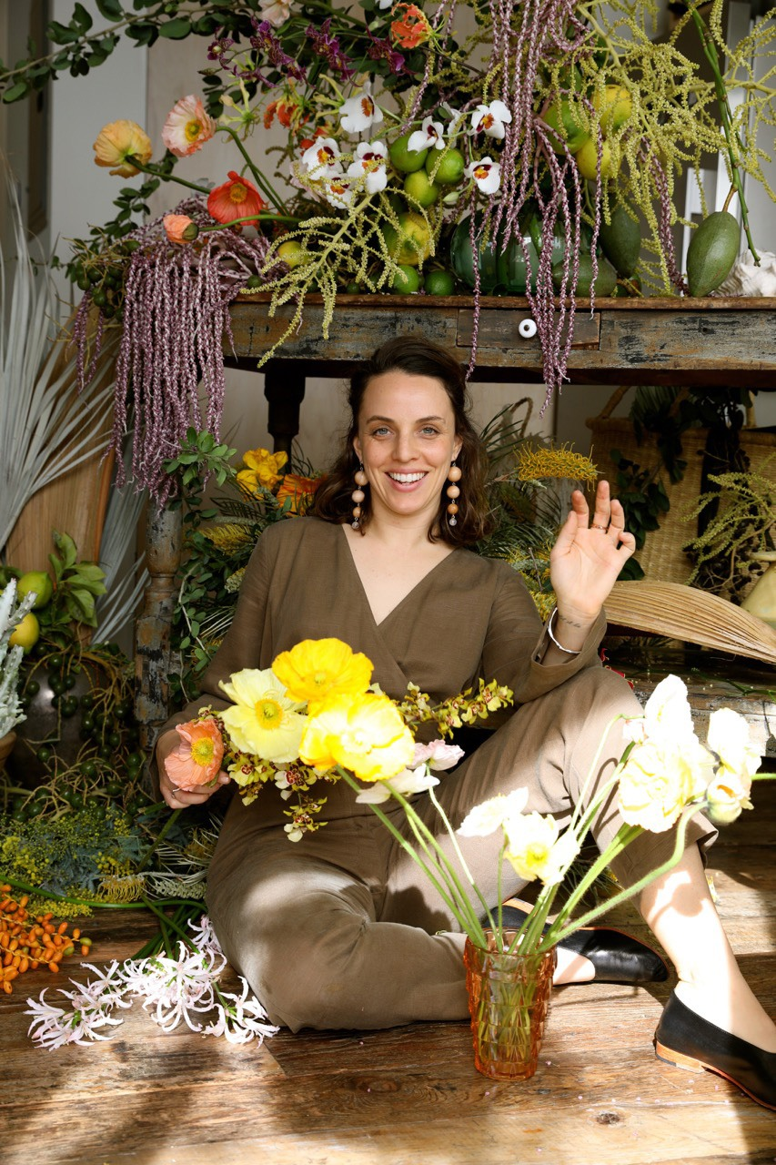 Sophia Moreno-Bunge surrounded by juicy winter florals, palm inflorescence and orchids; photo by Tierney Gearon