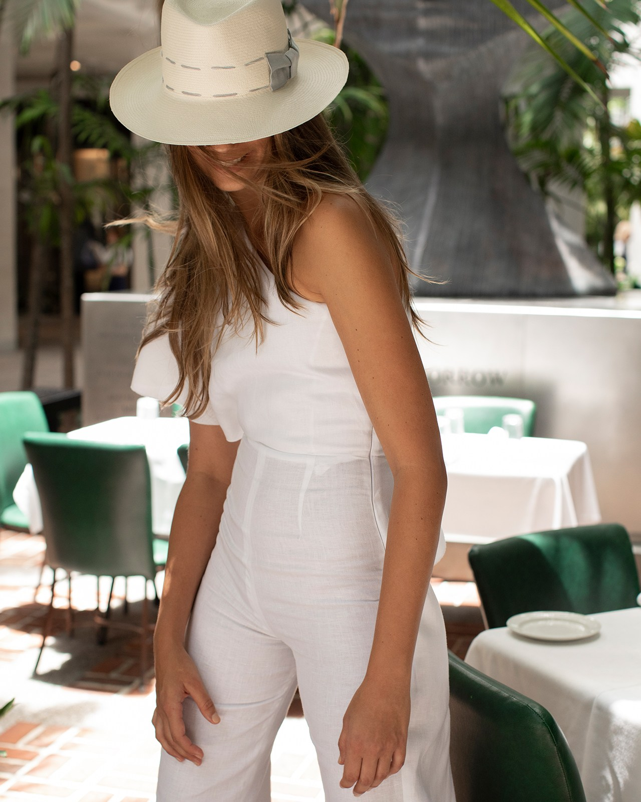 100% Capri linen jumpsuit styled with a gray-trimmed Panama hat