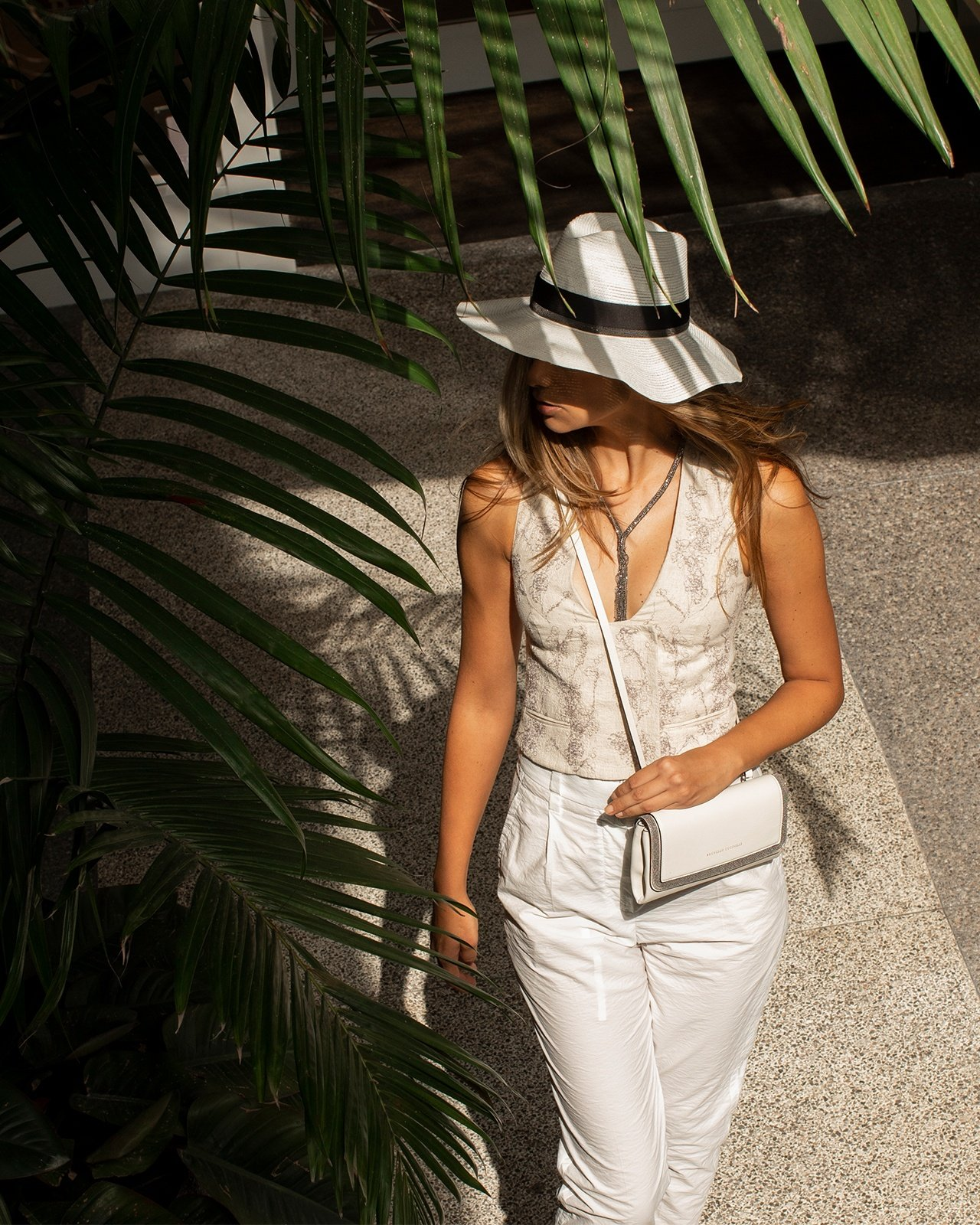 Brunello Cucinelli linen vest and cotton pants styled with a black-trimmed hat