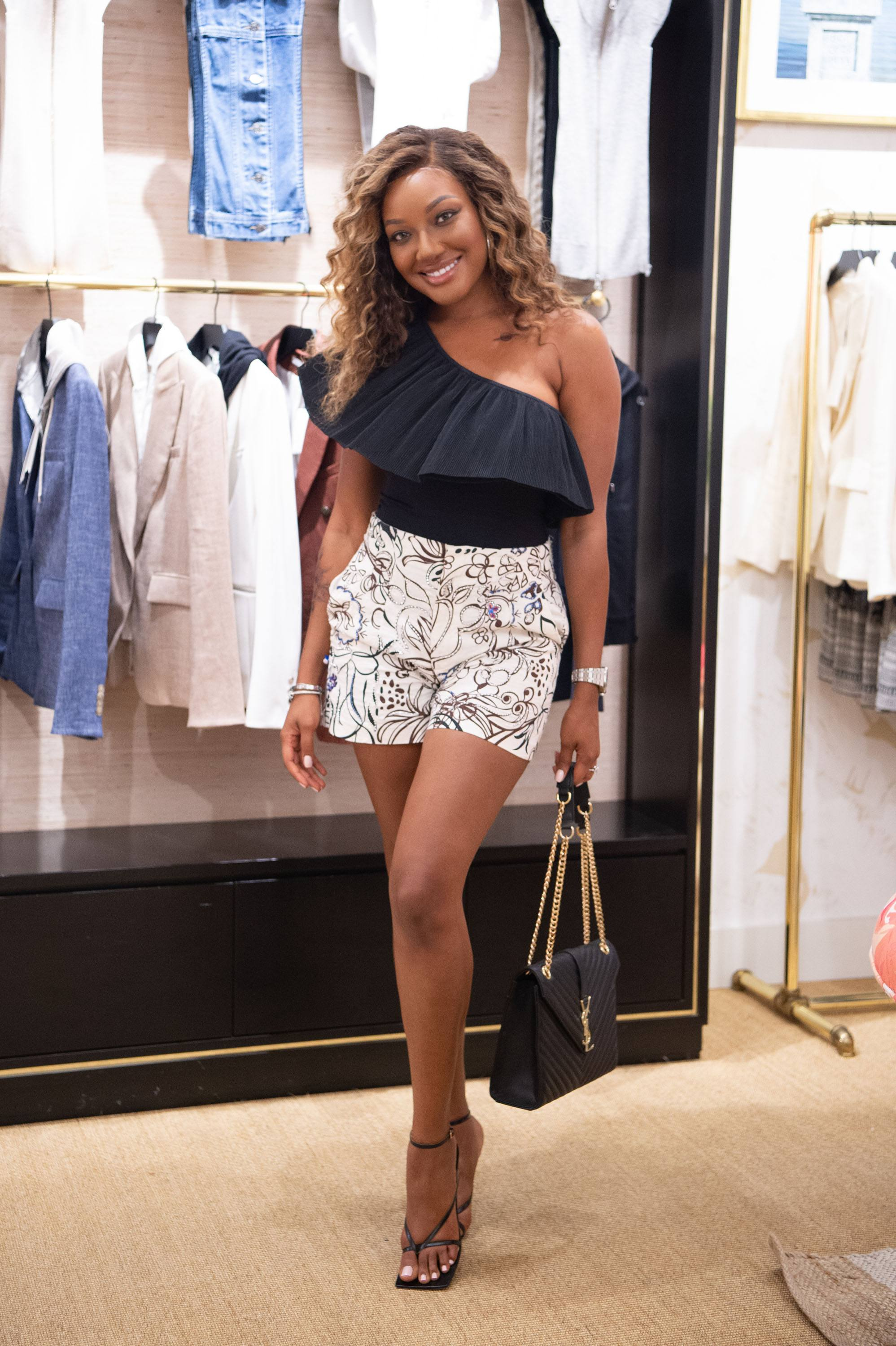 Woman poses in front of clothes rack inside Veronica Beard store