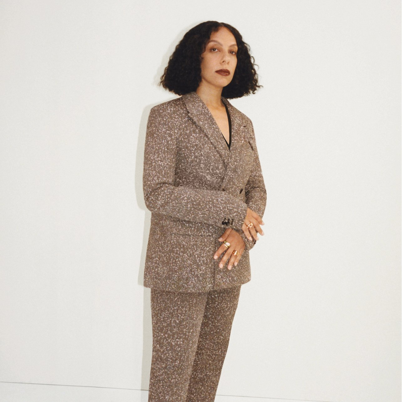 Woman poses wearing a brown pant suit with white speckled detailing