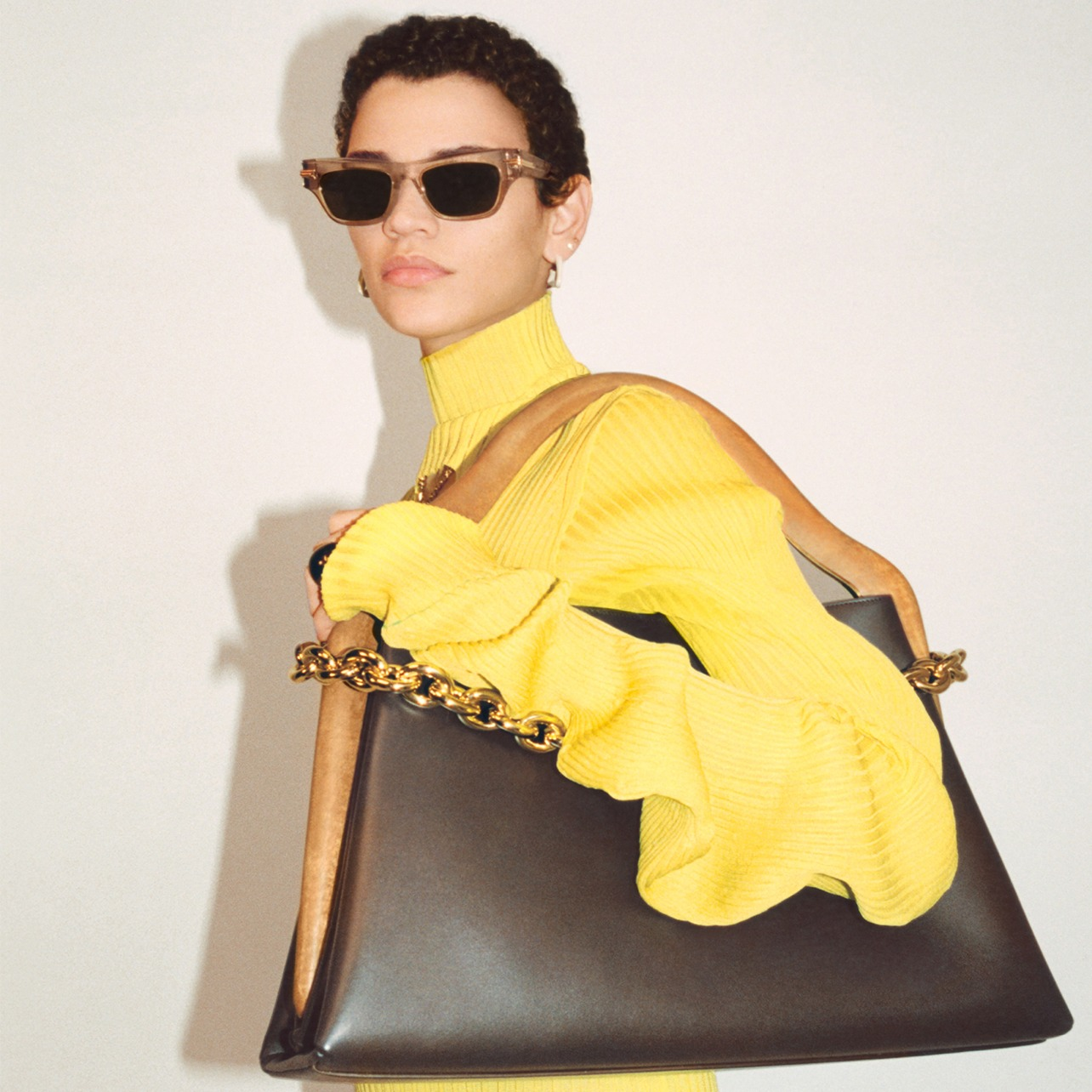 Woman poses in a high-neck yellow sweater dress while holding a large shoulder bag with gold chain detailing