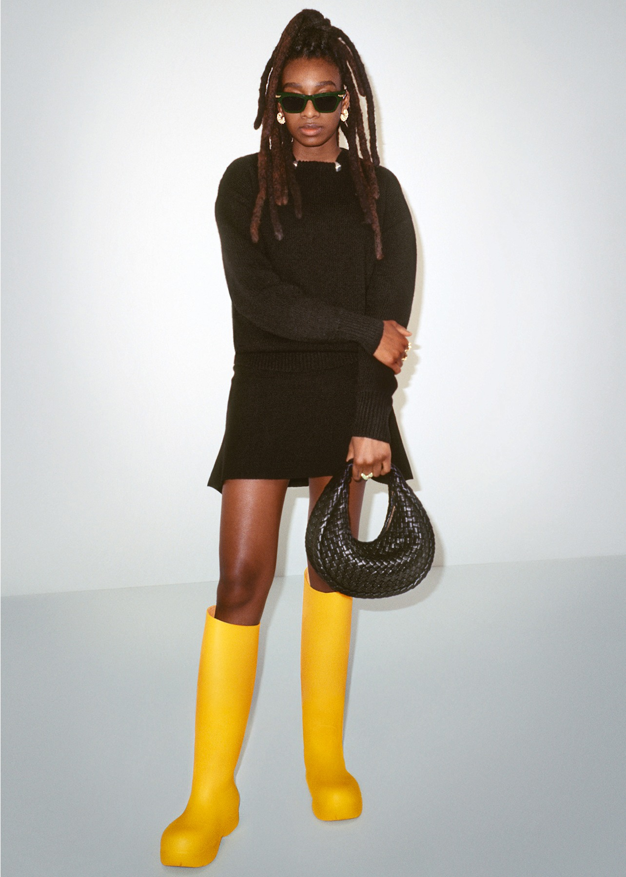 Model poses wearing a black sweater, black skirt, yellow knee-high rubber boots and holding a black woven top handle bag