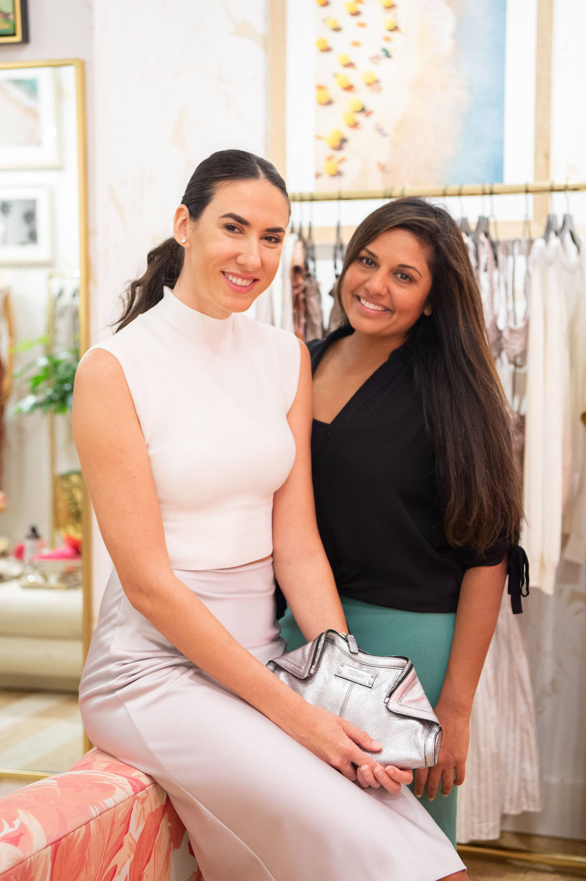 Two woman posing for a photo inside the Veronica Beard store
