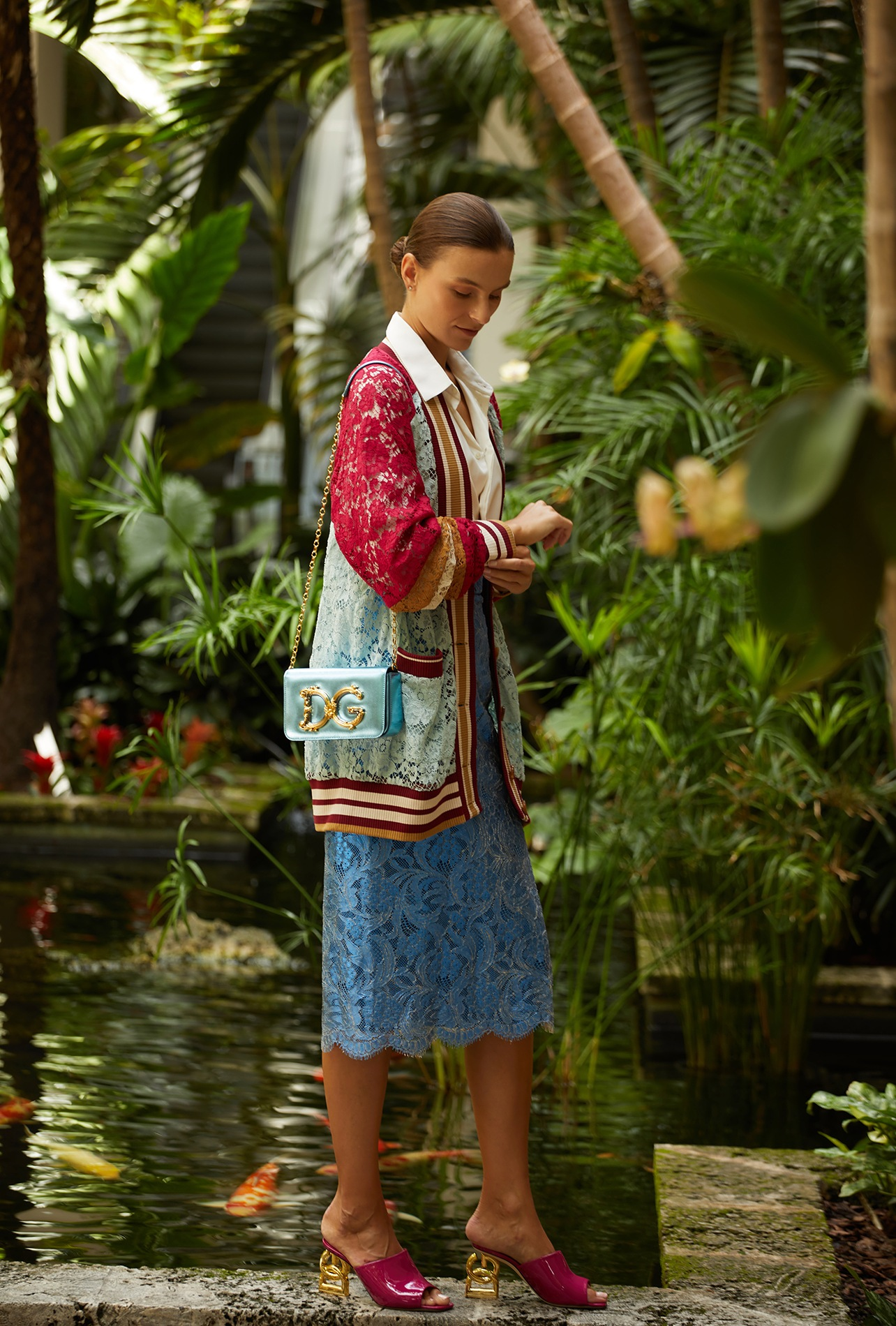 Dolce & Gabbana blue lace letterman cardigan, ivory silk blouse, blue lace skirt, gray leather bag with gold D&G detailing and pink mules with D&G logo heel