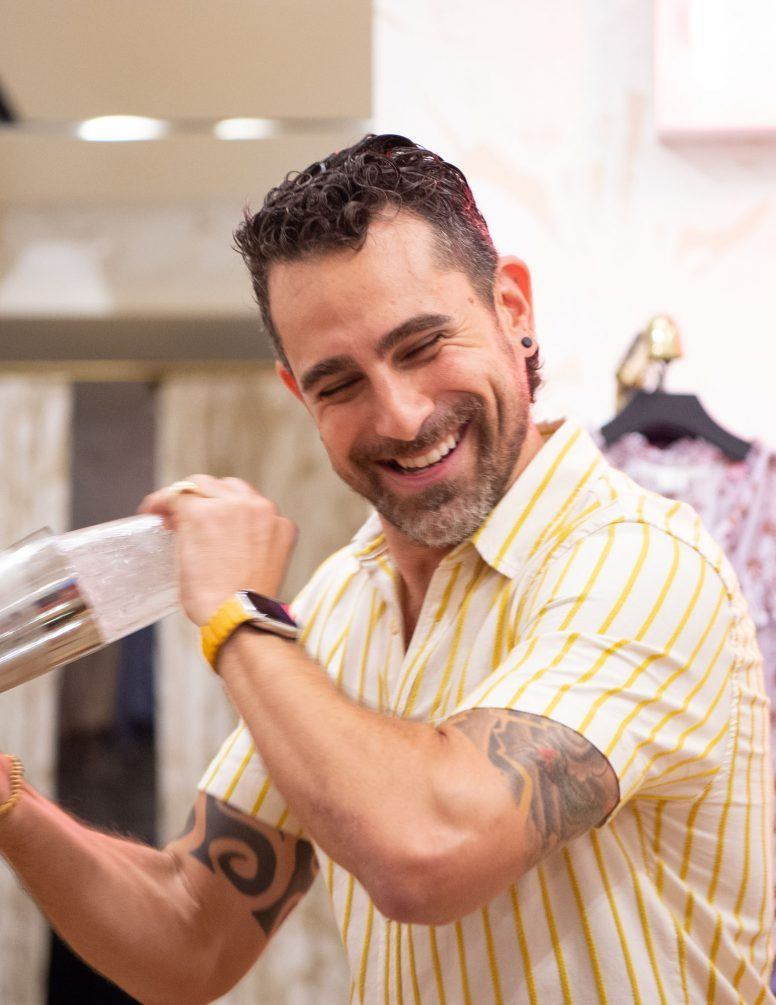 Man shaking a cocktail shaker while smiling