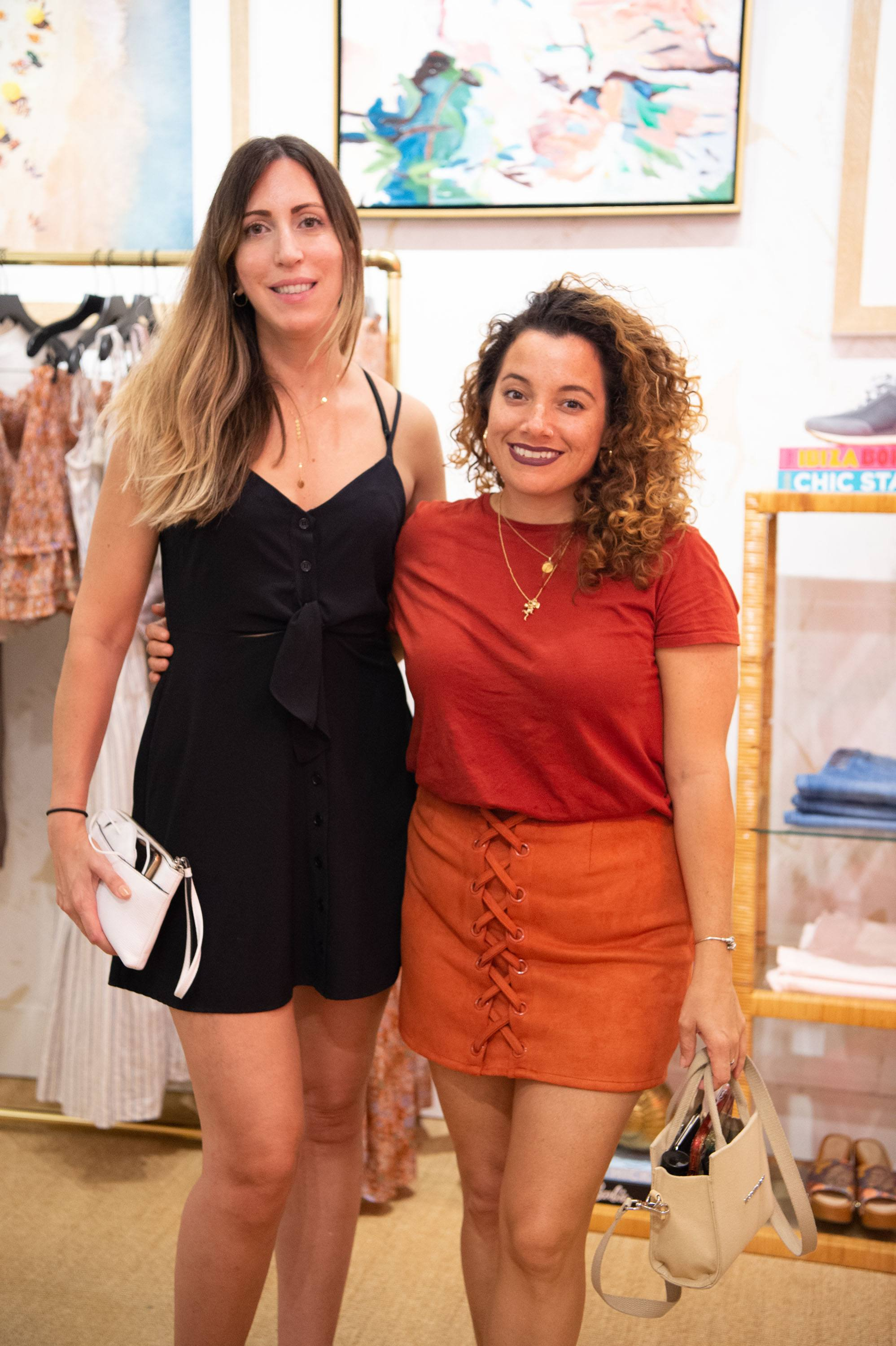 Two women smile and pose for a photo in the Veronica Beard store