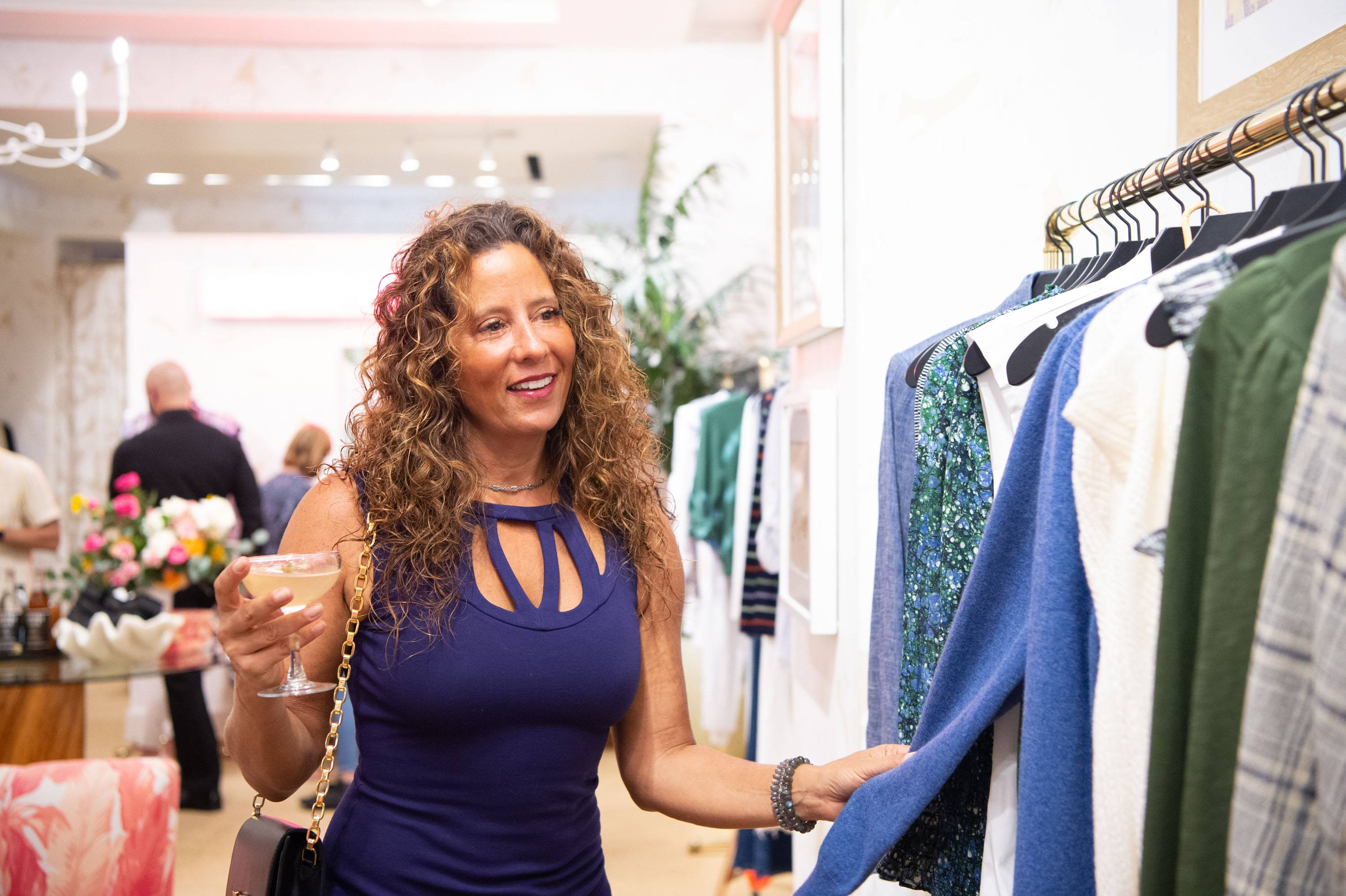 Woman is pictured smiling and browsing the Veronica Beard merchandise while holding a cocktail
