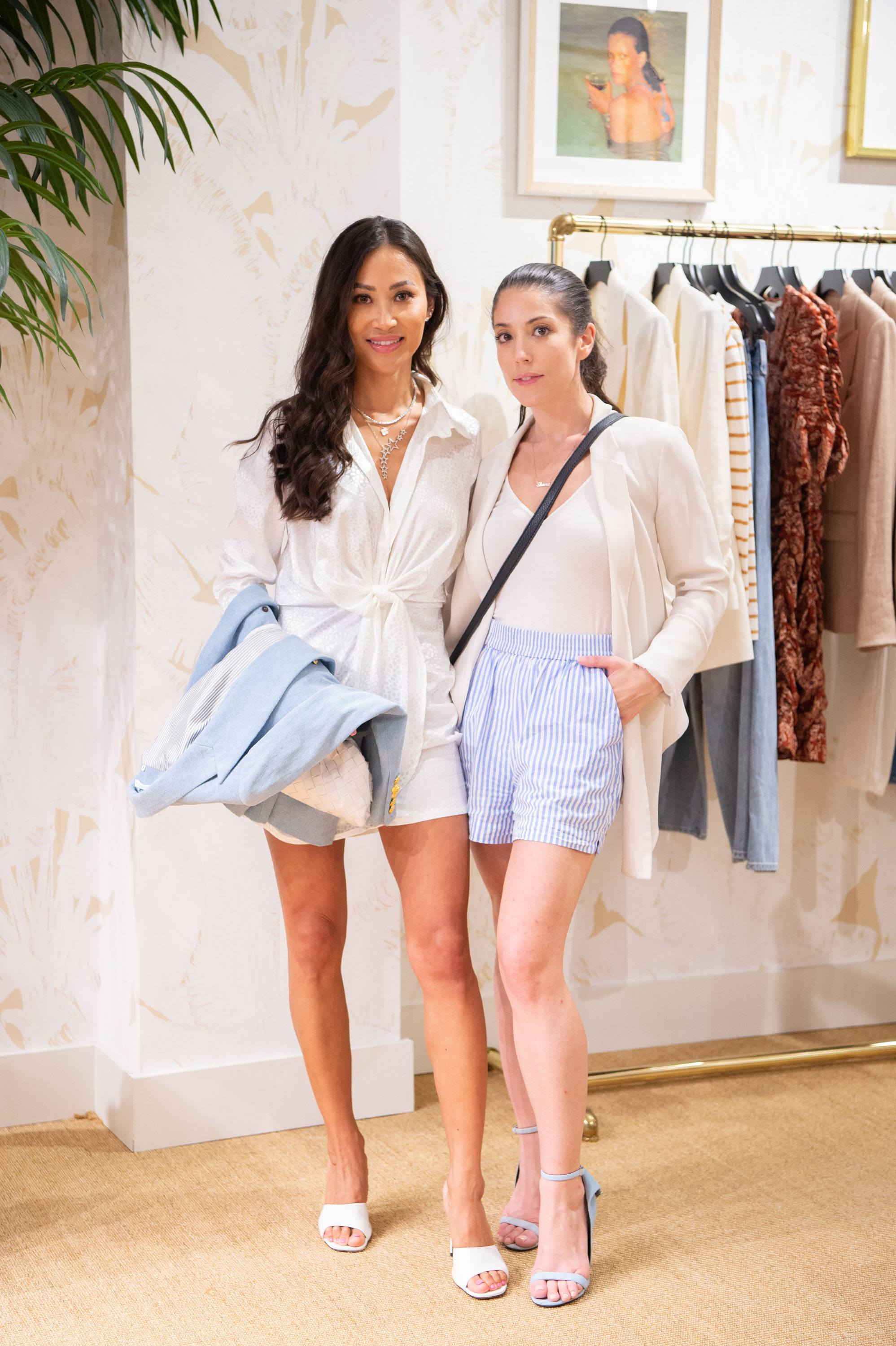 Two women pose for a photo in front of a merchandise rack inside the Veronica Beard store