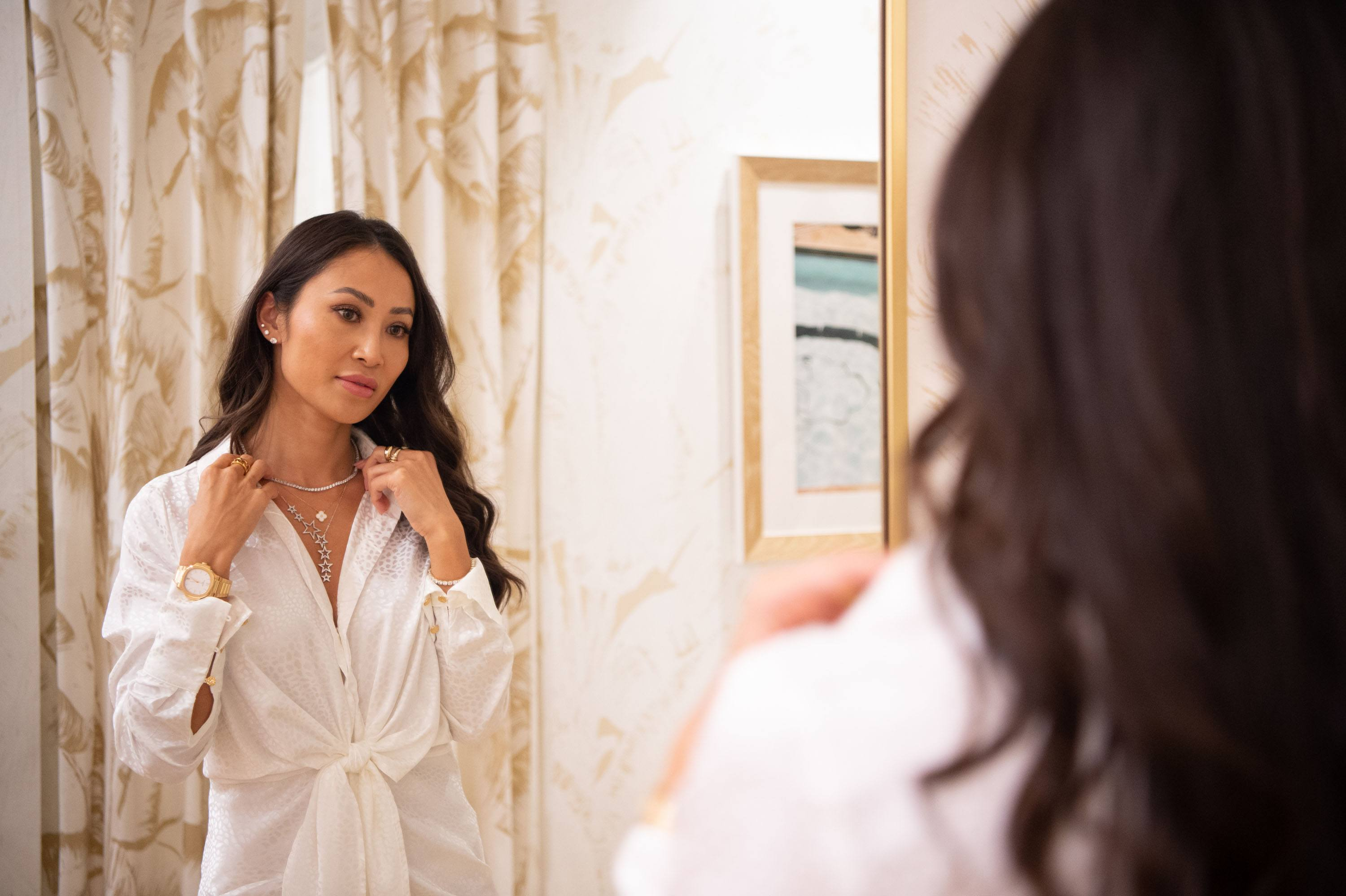 Woman poses in front of a mirror while adjusting her necklace