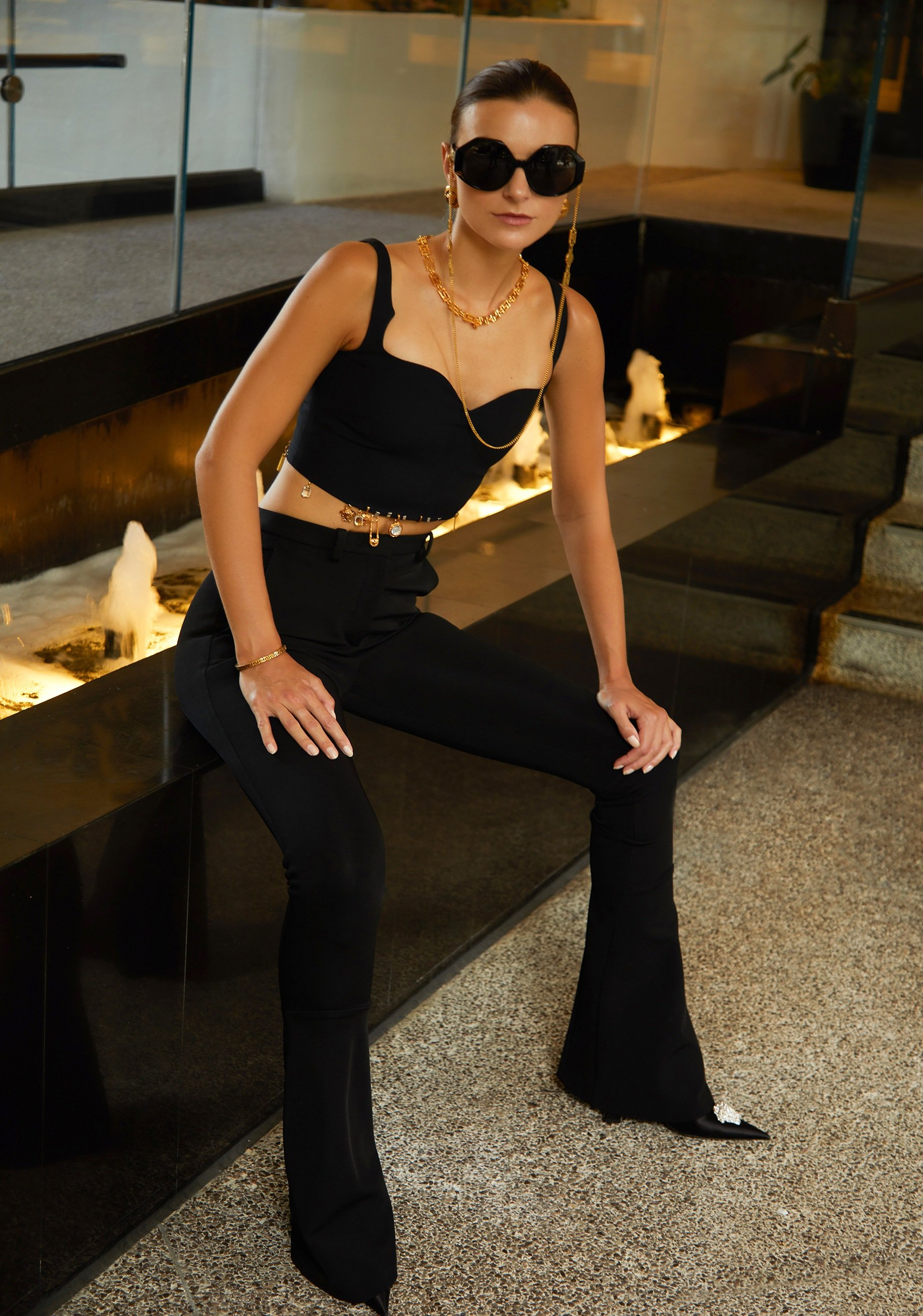 Versace black satin bustier top and pants with gold charm detailing, black pointed toe pumps with crystal La Medusa detail and black sunglasses with gold chain