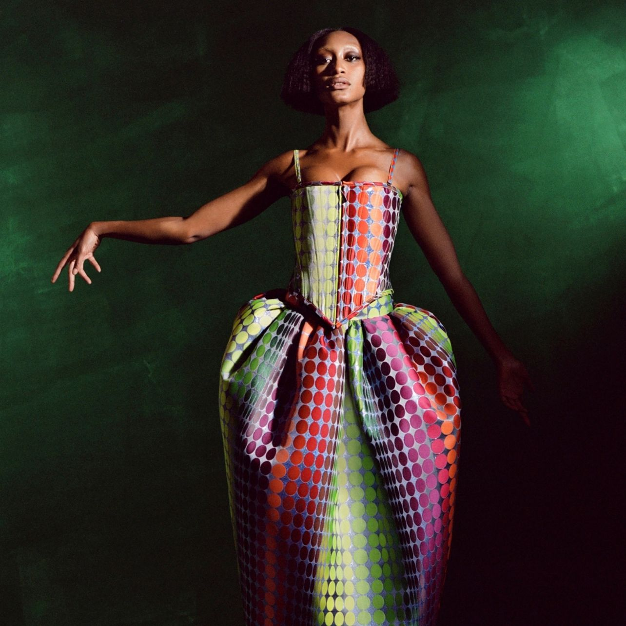 Woman poses wearing a structured dress with a multicolored dot pattern