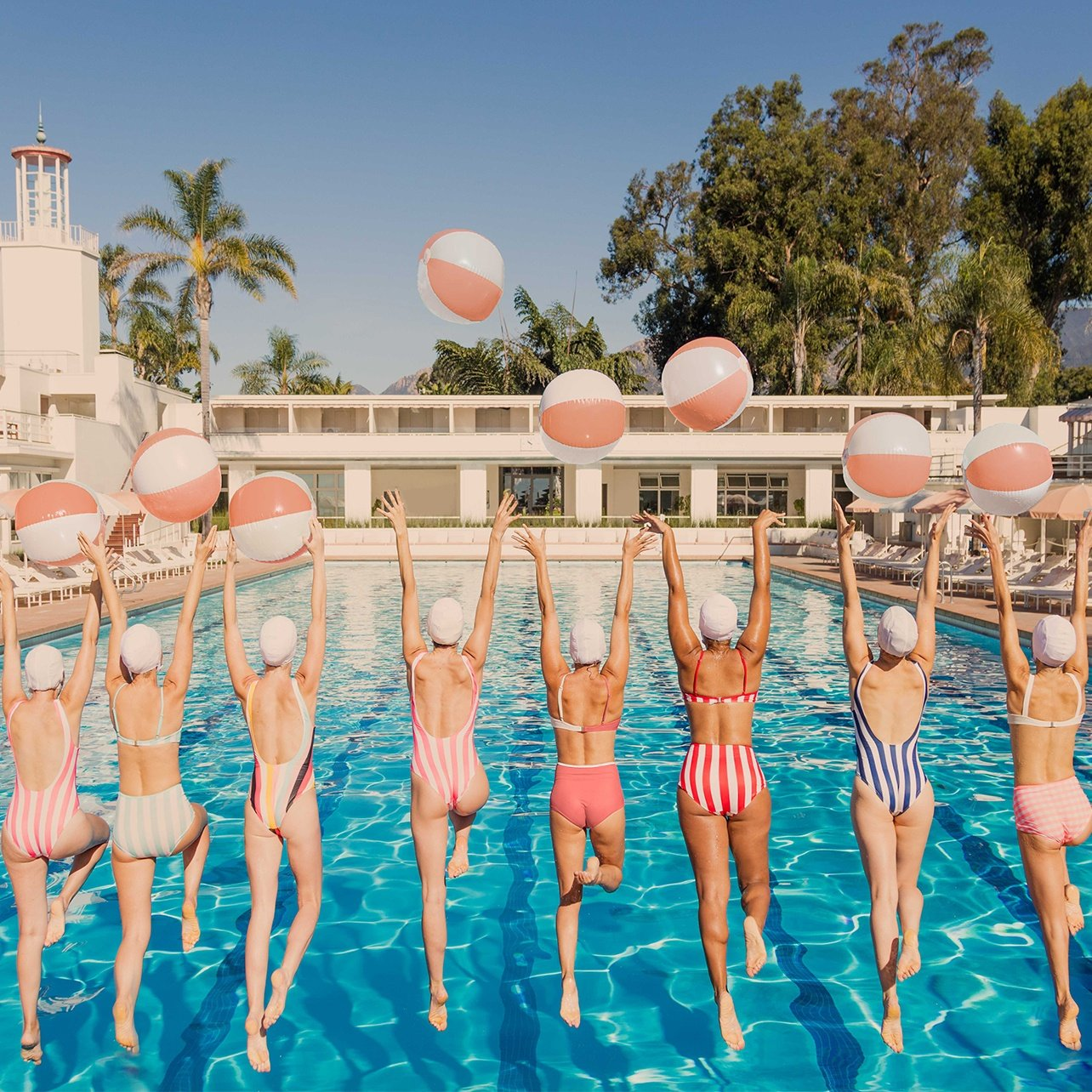 Group of women in striped bikinis jumping into a swimming pool with matching beach balls above their heads