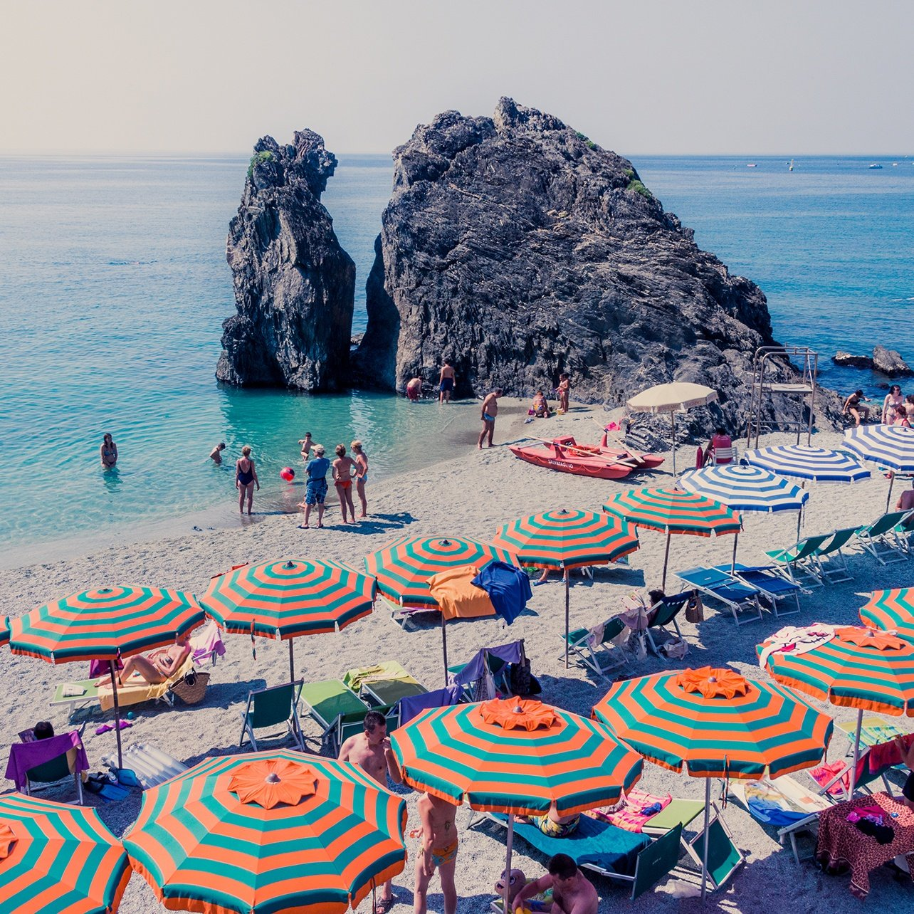 Photo of the Monterosso coast lined with mutli-colored umbrellas