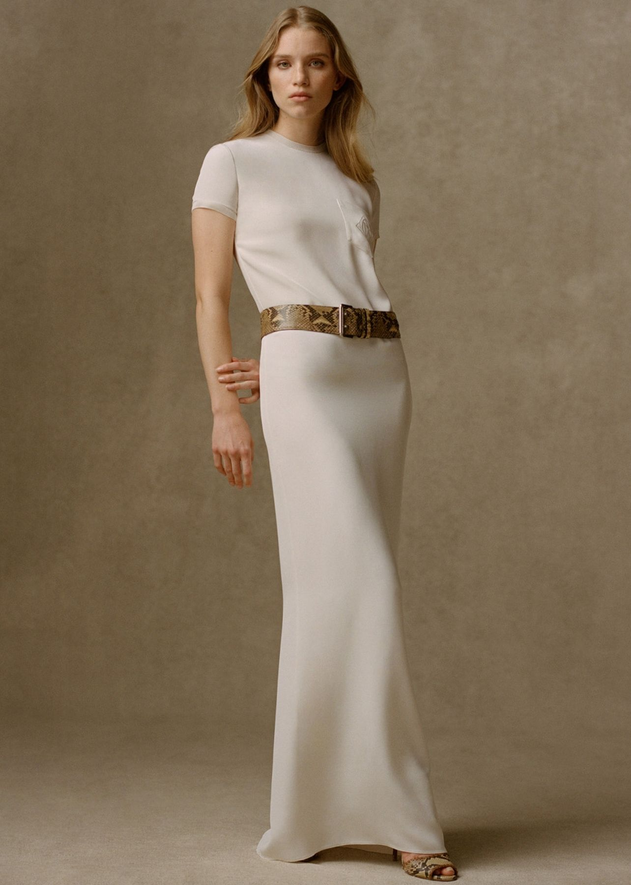Woman photographed in an ivory floor length dress paired with a snakeskin waist belt and matching sandals