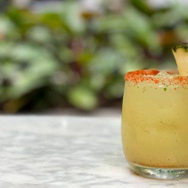 Cocktail pictured in front of palm leaves with a pineapple slice garnish