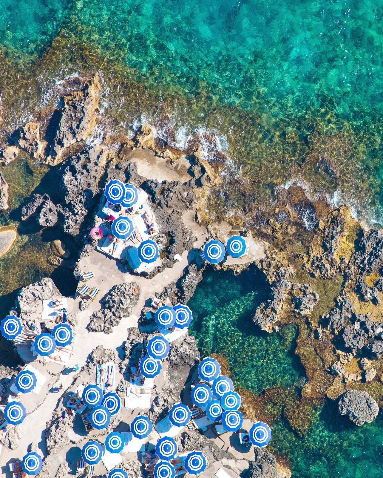 Arial photo of the Mediterranean coast with scattered blue umbrellas