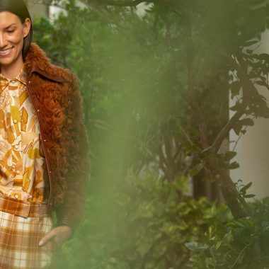 Woman is walking with a smile wearing a retro-style blouse, plaid trousers and a shearling jacket from Zimmermann